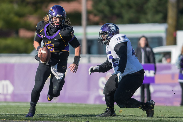 Minnesota State quarterback Ryan Schlichte scrambles away from Winona State's Quinton Reed during Saturday's game. With Nate Gunn sidelined, Schlichte played a bigger role than usual in the running game in the Mavericks 27-6 victory. Photo by Jackson Forderer