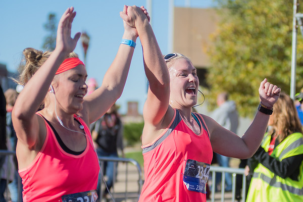 Willow Krogh (right) and Danielle Hager raise their hands as they cross the finish line during the Mankato half marathon. Photo by Jackson Forderer