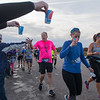 Richard Murray (1065) grabs a cup of water at the second water station along the half marathon course Sunday. Photo by Jackson Forderer