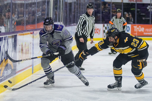 Minnesota State's Ian Scheid (18) chases the puck along the boards against Michigan Tech's Raymond Brice (23) in the second period. Photo by Jackson Forderer