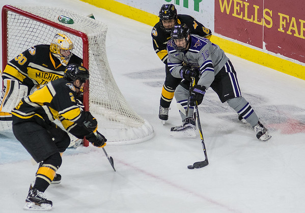 Reggie Lutz (16) of Minnesota State tries a wrap around shot against Michigan Tech goalie Patrick Munson (30) while being defended by Dylan Steman in the first period of Friday's game played at the Verizon Center. Photo by Jackson Forderer