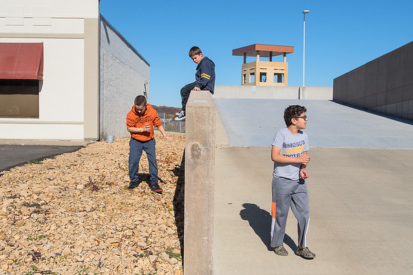 From left,  Archie Leboutillier, 9, Gordon Henry Leboutillier, 7, and Andrew Haefner, 11, play along the wall of the public safety parking ramp as marathon runners trickled in on Sunday. Photo by Jackson Forderer