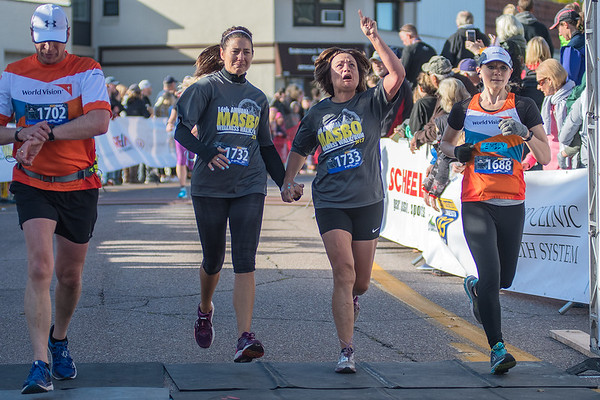 Monde Schwartz (1733) points her finger to the sky as she crosses the finish line with Alicia Truebenbach (1732) during the Mankato half marathon Sunday. Photo by Jackson Forderer