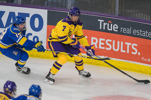 Minnesota State's Wyatt Aamodt looks to pass the puck to a teammate while being pressured by Alaska Fairbanks' Jake Gresch in the third period of Friday's game. Photo by Jackson Forderer