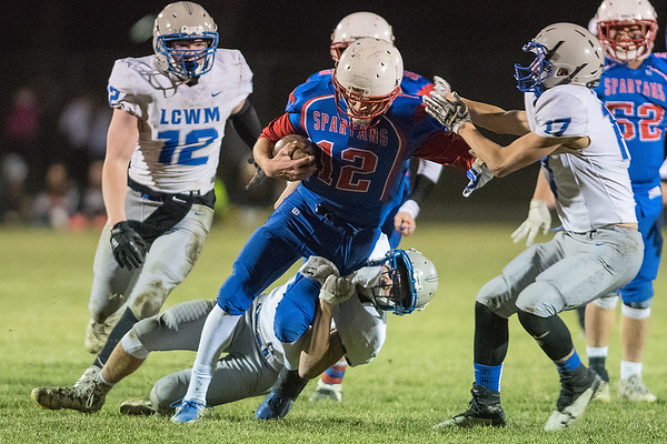 Lake Crystal-Wellcome Memorial's Landon Lantz (bottom) and Jayden Johnson (right) try to drag down Derik Miller of St. Clair/Loyola in Tuesday's Section 2AA playoff game. The consistent running game of the Spartans was the difference in their win over the Knights. Photo by Jackson Forderer