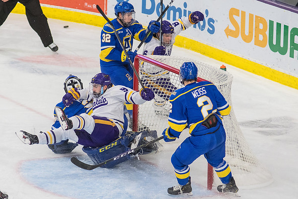 Minnesota State's Charlie Gerard topples onto the goalie from Alaska Fairbanks after having the puck. Gerard was called for charging on the play. Photo by Jackson Forderer