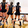 Mankato East's Claire Ziegler (13), Taylor Karge (15) and Jordan Kuster (3) watch as Mankato West's Abby Leitch lunges for the ball during their match Tuesday at the East gym.