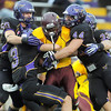 Pat Christman<br /> University of Minnesota Crookston's Tevin Kellum is brought down by Minnesota State's Kris Fleigle (50), Patrick Schmidt (3) and Jordan Campbell (44) during the first half Saturday at Blakeslee Stadium.