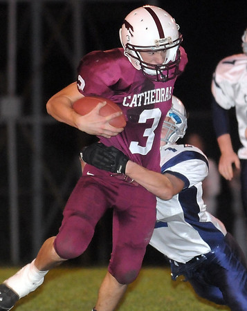 Pat Christman <br /> New Ulm Cathedral's Jacob Gangelhoff tries to shed the tackle of Minnesota Valley Lutheran's Chad Lease during the first half Friday.