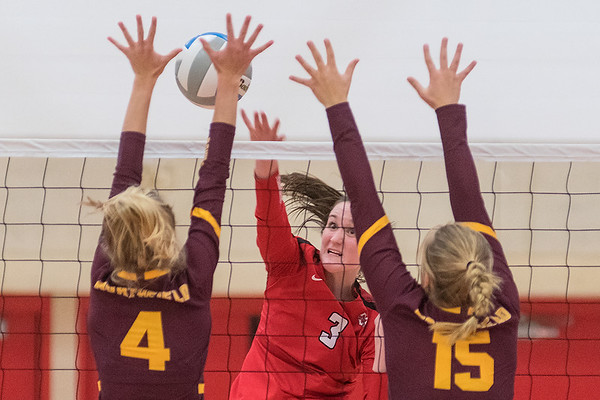Mankato West's Kennedy Geller (3) hits a spike past Northfield's Presley Fink (4) and Emma Roethler (15) in Tuesday's Big 9 matchup. Northfield won the match in three games. Photo by Jackson Forderer