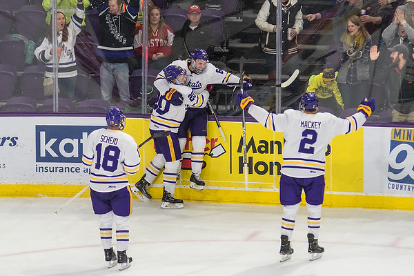 Minnesota State's Parker Tuomie is held up against the boards by teammate Marc Michaelis after Tuomie scored his second goal of the game against Boston University. The Mavericks rallied from a 3-2 deficit to win 4-3 in their first game of the season. Photo by Jackson Forderer