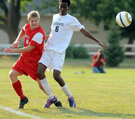 West's Paul Esslinger and East's Ahmeday Hassan go for the ball.