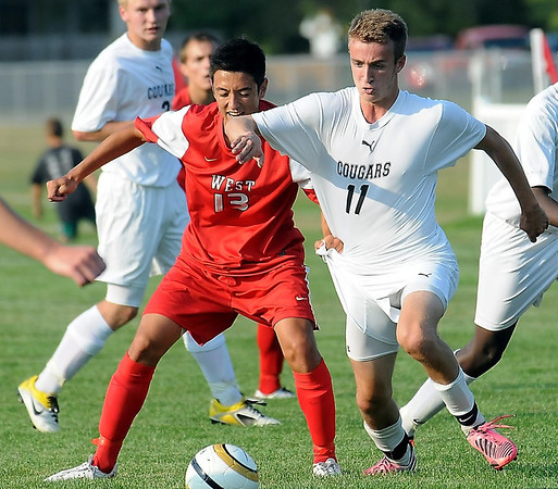 West's William Leitch has a handful of  East player Ben Schwartz's  jersey as they go for the ball.