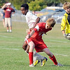 East's Mohamud Ahmed goes up against West's Andrew Opsal as East goalie Nick Olson looks on.