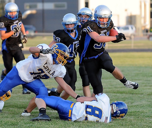 Lake Crystal-Wellcome Memorial running back Bryan Davis gets around Loyola defenders Charlie Lena (72) and Brian Baker.