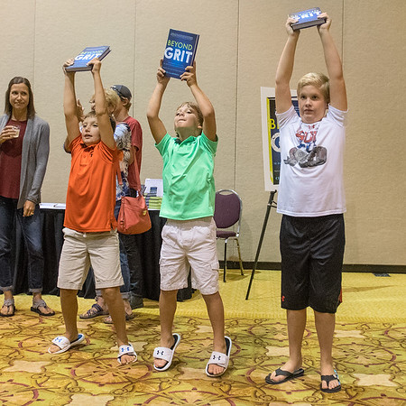 From left, Carter Kamphoff, 10, Blake Kamphoff, 8, and Jack Parker, 10, hold up a copy of Cindra Kamphoff's new book Beyond Grit as she panned across the audience for a Facebook Live feed at the book launch on Thursday. Carter and Blake are Cindra's sons, whom she gave thanks to at the book launch. Photo by Jackson Forderer