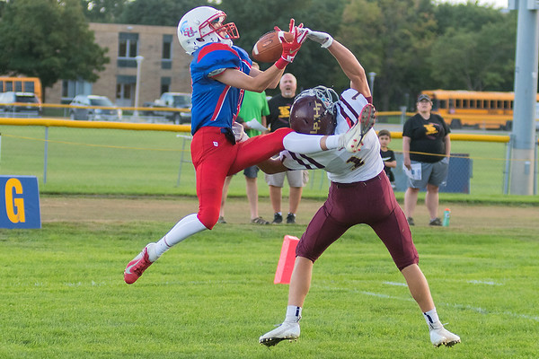 St. Clair/Loyola's Mathew Helget pulls in a catch in the end zone over Lester Prairie/Holy Trinity's Parker Bayerl during Friday's game played at Loyola. Photo by Jackson Forderer