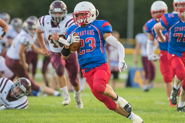 St. Clair/Loyola's Noah Schruin breaks into the secondary of the Lester Prairie/Holy Trinity defense in the first half of Friday's game. Schruin ran for three touchdowns in the Spartans inaugural win. Photo by Jackson Forderer
