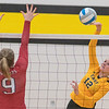 Mackenzie Schweim (12) of Mankato East spikes a ball against a block from Austin's Lily Holtz during Thursday's game played at East. East won the match in three straight sets. Photo by Jackson Forderer