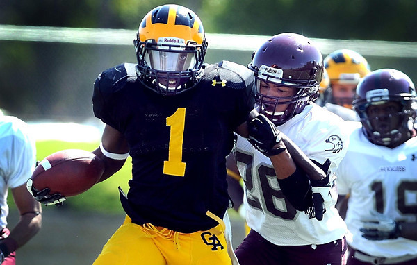 Gustavus Adolphus College's Phillip Butler is pursued by Augsburg's Michael Busch during a first half run Saturday at Hollingsworth Field.