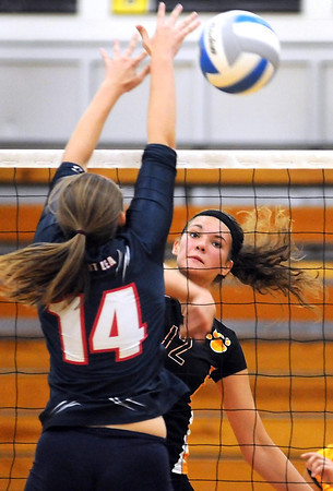 Mankato East's Allison Taylor hits the ball past Albert Lea's Kassi Hardies during their first game Thursday at the East gym.