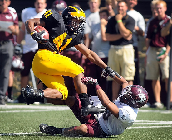 Gustavus Adolphus College running back Jeff Dubose trips over Augsburg's Avery Dorsett during the first half Saturday.