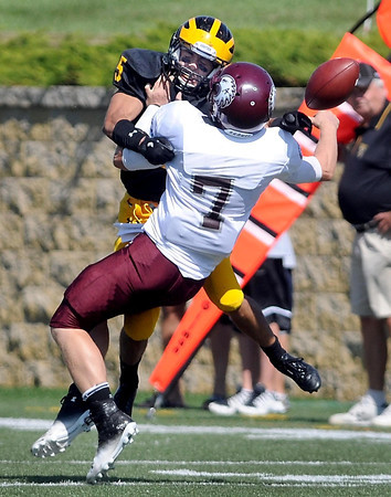 Augsburg quarterback Tim Lund loses the ball after he is hit by Gustavus Adolphus College's Torey Asao during the first half Saturday at Hollingsworth Field.