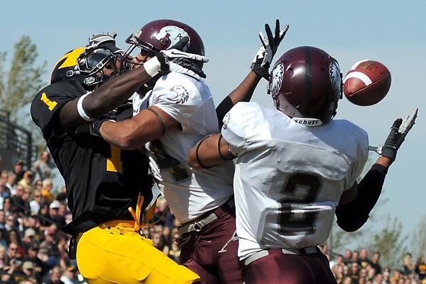 Gustavus Adolphus receiver Phillip Butler (1) is blanketed by a pair of Augsburg defenders during the first half Saturday.
