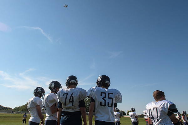 St. Peter football players stand on the sidelines during practice while a drone (top) flown by Ethan Volk takes footage of the practice overhead. Photo by Jackson Forderer
