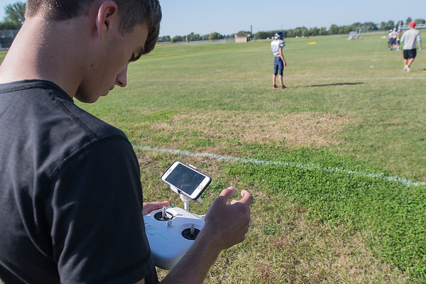 Ethan Volk looks at the screen on a phone while flying a drone over the St. Peter football team practice on Wednesday. Photo by Jackson Forderer