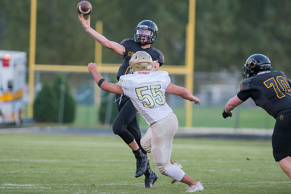 Mankato East quarterback Riley Gruenes makes a pass while being pressured by Rochester Mayo's Sheldon Day (55) in the first half of Friday's game. The Cougars fell to the Spartans 40-13. Photo by Jackson Forderer