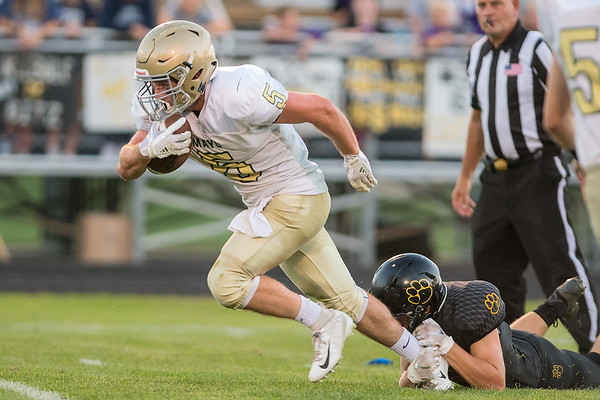 Mankato East's Isaac Turner hangs onto Rochester Mayo's Jack Murphy during a punt return in Friday's game. East fell to Mayo 40-13. Photo by Jackson Forderer
