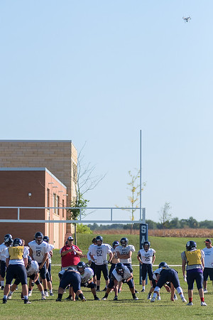 A drone (upper left) is flown over the St. Peter football team by Ethan Volk during the team's practice on Wednesday. The team utilizes the drone footage to analyze its plays. Photo by Jackson Forderer