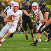 Mankato West quarterback Jack Foster (left) escapes the pocket and runs against Mankato East during a game played on Sept. 7 at Blakeslee Stadium. Photo by Jackson Forderer