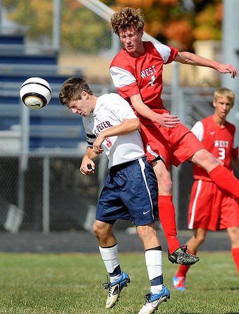St. Peter's Marty Johnson (left) heads the ball away from Mankato West's Kennedy Maker during the first half Saturday in St. Peter.