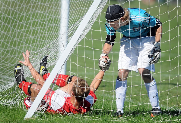 Pat Christman <br /> Mankato East goalie Derek Helms helps Mankato West's Jacob Makela out of the net after a shot during the first half Saturday.