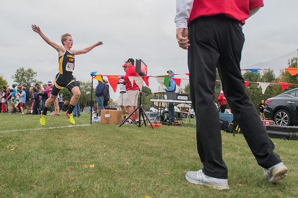Mankato East's xxx raises his arms as he crosses the finish line at the West Cross Country Invitational. The East boys cross country team took first place. Photo by Jackson Forderer