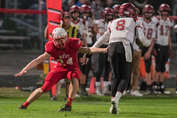 Mankato West's Dawson Frericks (24) tries to slow down New Prague's quarterback Nathan Berg (8) during the first half of Friday's game. West won the game 41-7. Photo by Jackson Forderer