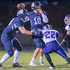 St. Peter quarterback Wyatt Olson (18) throws to a receiver while being pressured by New Ulm's Dalton Helget (22) in the second quarter of play during Friday's game. Photo by Jackson Forderer