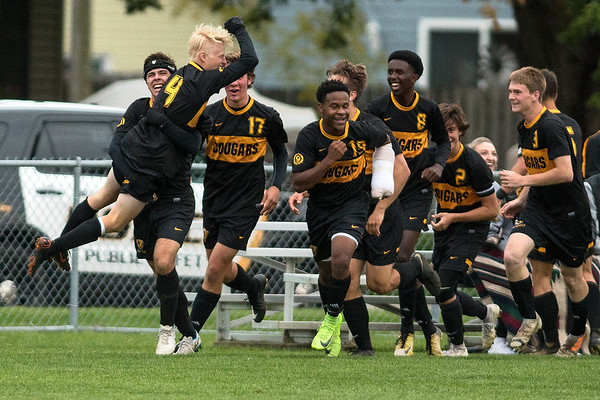 Koby Gagnon picks up Seth Hardesty as they celebrated Hardesty's goal with other Mankato East teammates. Hardesty's goal put the Cougars up 2-0 to secure a win over Rochester Lourdes on Thursday. Photo by Jackson Forderer