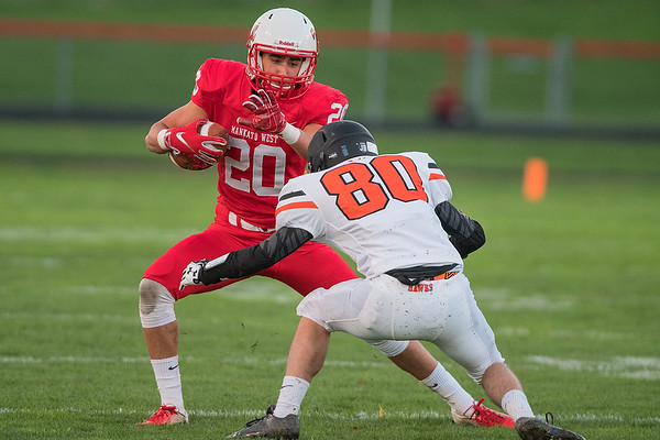 Mankato West's Cole Reinardy (20) tries to get past Winona's Levi Schewe (80) after catching a short pass in the first half. Photo by Jackson Forderer