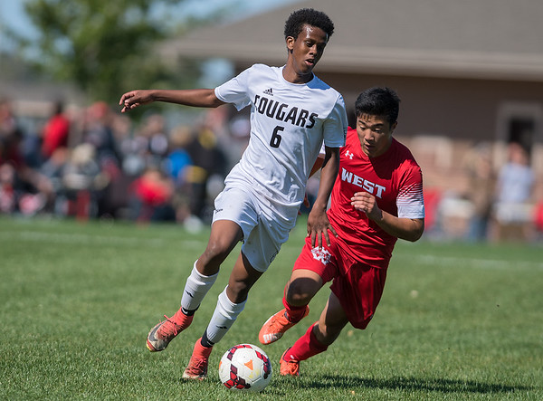 Mankato East's Isak Abader (left) dribbles past Mankato West's Sam Neumann in the second half of play of Saturday's cross-town matchup. The game ended in a 0-0 tie. Photo by Jackson Forderer