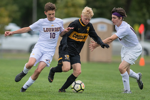 Mankato East's Seth Hardesty tries to split Rochester Lourdes defenders Matt Steinmetz (left) and Jared Anderson. Hardesty would later score the Cougar's second goal of the game. Photo by Jackson Forderer