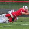 Wyatt Block of Mankato West stretches the ball out over the goal line for the Scarlets first touchdown while Winona's Zaid Elsabbagh tries to tackle him. West lost the game to the Winhawks 25-14. Photo by Jackson Forderer