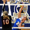 Mankato Loyola's Alli Menke tries to hit the ball past the block of Alden-Conger's Brooke Reyerson during their first game Thursday at the Fitzgerald gym.