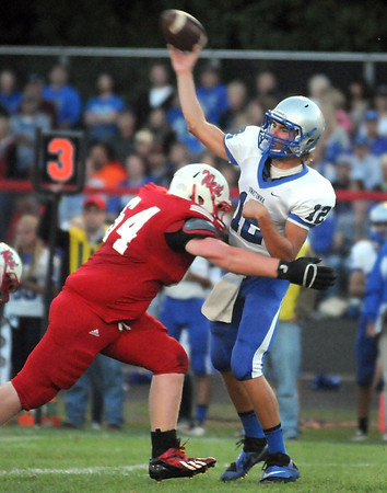 Pat Christman<br /> Owatonna quarterback Ian Langeberg is hit by Mankato West's Alex Berglin as he throws during the first half Friday.