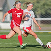 Mankato West's McKenna Buisman (3) tries to get past Austin defender Clara Munger (10) during Thursday's game. Buisman scored 3 goals for the Scarlets in their win. Photo by Jackson Forderer