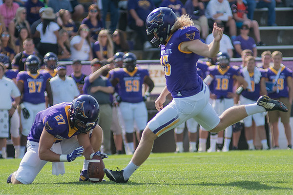 Minnesota State's Casey Bednarski (15) kicks an extra point as Justin Arnold (27) holds the ball in the third quarter. Earlier in the game, Bednarski kicked a 63-yard field goal, which set a school and NSIC record. Photo by Jackson Forderer