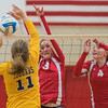 Mankato East's Madie Clarke (11) tries to tip the ball past Mankato West's Kennedy Geller (3) and Emily Bergeman (4) in the fifth game of Thursday night's match. The Scarlets won the fifth and final game 15-13. Photo by Jackson Forderer