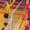 Mankato East's Jensina Pasker tips the ball over the net while Mankato West's Ellie Blackman (top) and Kenzie Grunst wait to defend the ball during Thursday's rivalry game. West won the contest in five games. Photo by Jackson Forderer